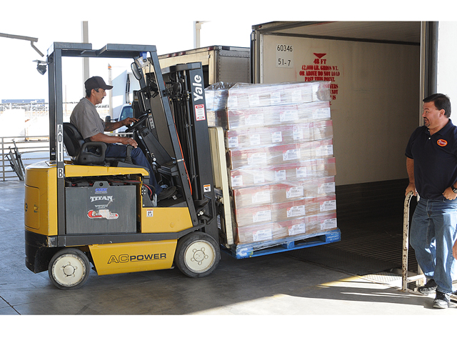 We got chicken! -- As Tyson Foods, Inc., truckdriver Dustin Crawford (right) looks on, Yuma Community Food Bank forklift operator Miguel De La Cruz removes a pallette of chicken from the back of a semi truck trailer to be stored inside the Food Bank warehouse Thursday morning. Tyson Foods donated 30,000 pounds of chicken to the Food Bank as part of an effort to feed people in need and to promote pulic awareness of hunger in America. In September Tyson Foods conducted a Facebook poll in which people were asked to vote for the food bank they would support to get a truckload of food. Ten food banks were selected to be in the poll, from among the most food insecure communities in the U.S. The top three vote-getters, including Yuma Community Food Bank, are getting a truckload of food this month. The top three vote getters in the poll were Food Bank of the Albemarle, Elizabeth City, N.C. (9,467 votes); Yuma Community Food Bank (9, 435 votes); and Mississippi Food Network, Jackson, Miss. (3, 425 votes). Photo by Ra
